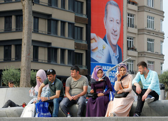 People rest in a park as an election poster for Turkey's President Tayyip Erdogan is seen on the background in Istanbul