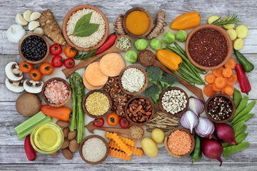 Health food for fitness concept with fruit, vegetables, pulses, herbs, spices, nuts, cereals, grains, olive oil and himalayan salt. High in antioxidants, fibre, smart carbs, minerals and vitamins.