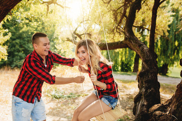 A loving couple on a swing near a tree. Fun and laughter. Young woman swinging on a swing, and boyfriend pushing her.