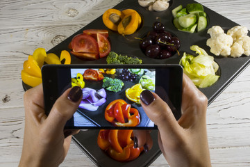 Girl taking picture of vegetarian food on table with her smartphone. women's hands photographed on the smartphone fruits and vegetables
