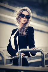 Young fashion blond business woman in sunglasses walking in city street