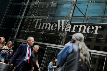People pass by Time Warner entrance in the Manhattan borough of New York City, New York