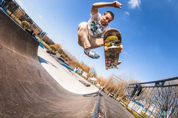 Skateboarder make trick boneless, high jump in mini ramp in skatepark