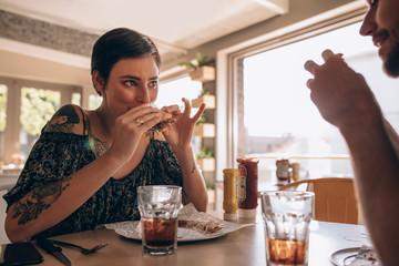 Foto op Canvas Kruidenierswinkel Woman having burger with boyfriend at restaurant