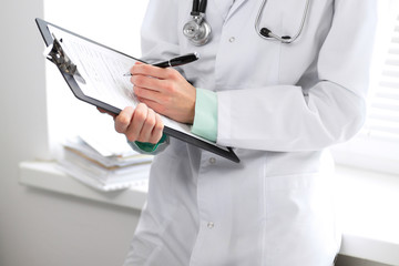 Female doctor filling up medical form on clipboard closeup.  Healthcare, insurance and medicine concept