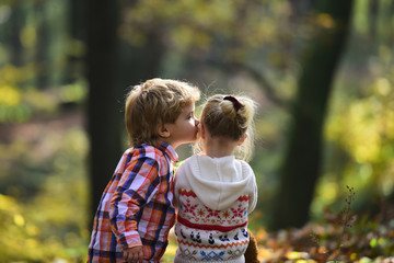 Little boy kiss small girl friend in autumn forest. Brother kiss sister with love in woods. Valentines day concept. Family love and trust. Childhood friendship and children early development