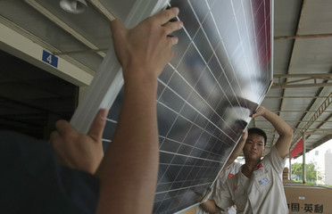 Employees examine newly-made solar panels before boxing for shipment at a factory of Yingli Solar in Baoding
