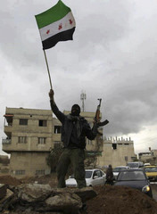 A Syrian soldier, who has defected to join the Free Syrian Army, holds up his rifle and waves a Syrian independence flag in the Damascus suburb of Saqba