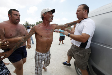 A camper grabs a man, who is taking part in a protest against camping on the beach, in Marsaxlokk