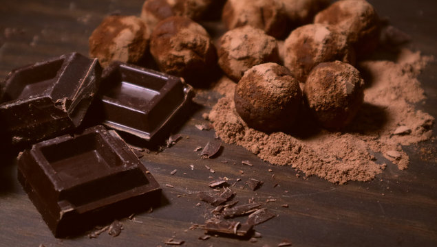 Chocolate truffles and dark chocolate on rustic dark wooden background.