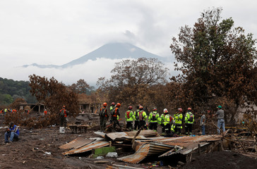 Rescue workers search for missing families at the area affected by the Fuego volcano at San Miguel Los Lotes