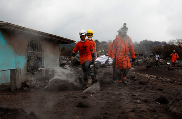 Rescue workers carry human remains at an area affected by the Fuego volcano at San Miguel Los Lotes in Escuintla