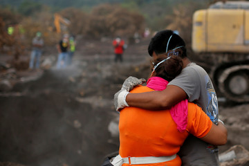 Eva Ascon, is embraced by a family member as rescue workers search for her rest of her family at the affected by the Fuego volcano at San Miguel Los Lotes in Escuintla