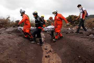 Rescue workers carry human remains at the affected by the Fuego volcano at San Miguel Los Lotes in Escuintla