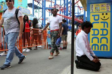 Hakeem Wazadally, 20, prays at Coney Island while celebrating Eid Al-Fitr at Luna Park in Coney Island, Brooklyn, New York