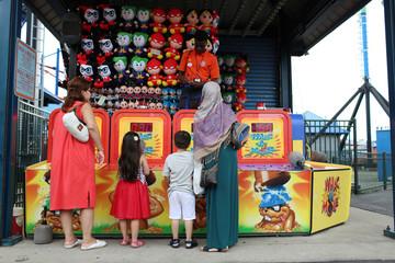 Muslim families celebrate Eid Al-Fitr at Luna Park in Coney Island, Brooklyn, New York