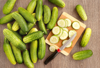 Cucumbers are cut on a cutting board. View from above. A lot of fresh cucumbers sliced on a cutting board for cooking dishes. Vegetables for a healthy diet.