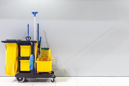 Mop bucket and set of cleaning equipment and sign of men toilet on the wall in the airport