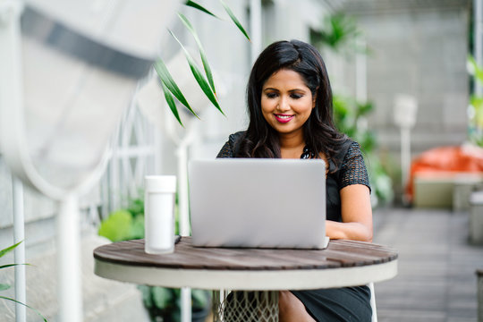 A confident and successful Indian woman (professional or business woman) is sitting and working on her laptop in the day.