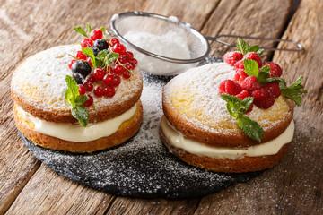 homemade sandwich Victoria cake with fresh berries and mint closeup. horizontal