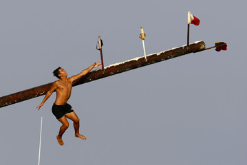 "A competitor slips off the ""gostra"" during the religious feast of St Julian outside Valletta"