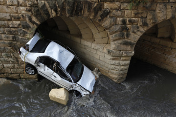 A heavily damaged car rests against a tunnel after being carried away by flash floods in Birkirkara