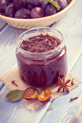 Vintage photo, Fresh plum marmalade or jam in jar, spices and ripe fruits in wicker basket, healthy sweet dessert