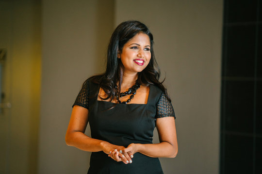 Professional Linkedin portrait head shot of a confident Indian Asian business woman against a plain backdrop.