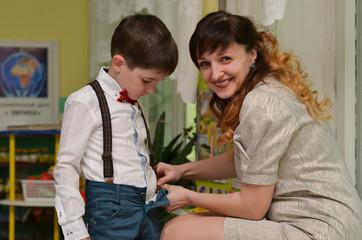 happy mother dresses the boy in school