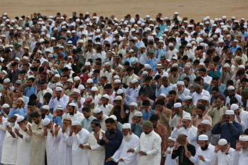 Men attend Eid al-Fitr prayers at a playground in Karachi