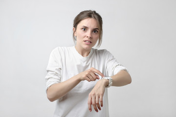 Young pretty caucasian student is angry because of being late. She is showing time on her watch.