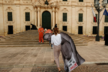 Activists from anti-corruption group Il-Kenniesa carry cardboard cut-outs of Cardona, Mizzi and Schembri during a protest marking eight months since the assassination of anti-corruption journalist Daphne Caruana Galizia, in Valletta