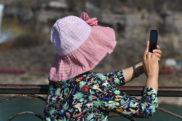 A chinese woman takes a picture of the Niagara-Falls in Camada