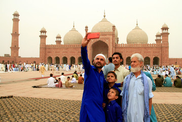 People take selfie as they attend Eid al-Fitr prayers at the Badshahi Mosque in Lahore