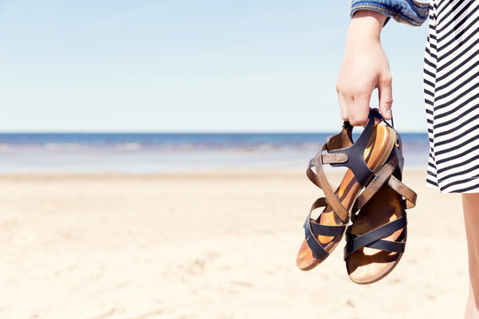 Woman on the beach holding her sandals at sunny summer day