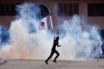 A demonstrator holds a banner as he runs amid smoke from a tear gas shell fired by the Indian police during clashes after the Eid al-Fitr prayers in Srinagar