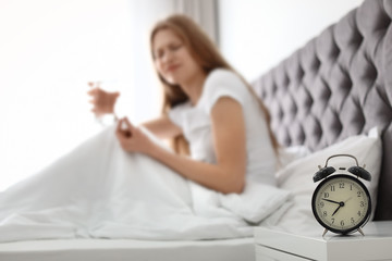 Alarm clock on nightstand of young woman suffering from headache