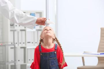 Doctor measuring little girl's height in hospital