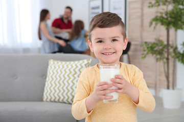 Cute little boy with glass of milk at home