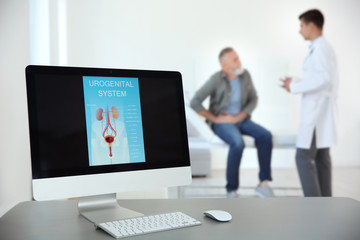 Computer monitor with picture of urogenital system and blurred people on background