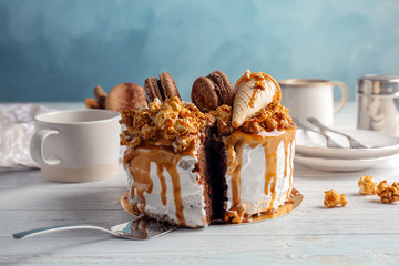 Delicious homemade cake with caramel sauce and popcorn on table