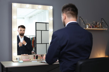 Young handsome man near mirror in makeup room