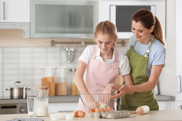 Mother and her daughter preparing dough at table in kitchen