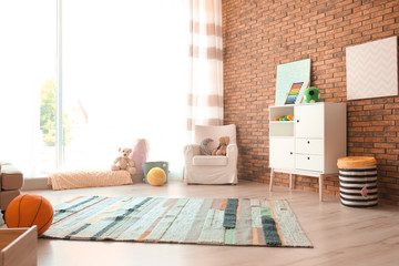 Stylish child room interior with comfortable armchair