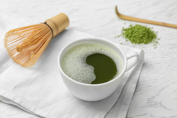 Cup of fresh matcha tea and chasen on table