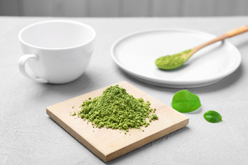 Wooden board with powdered matcha tea on table