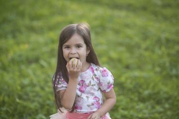 Girl eat apple on natural background, vitamin