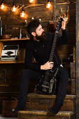 Favourite activity. Man bearded musician enjoy evening with bass guitar, wooden background. Man with beard holds black electric guitar. Guy in cozy warm atmosphere play relaxing soul music