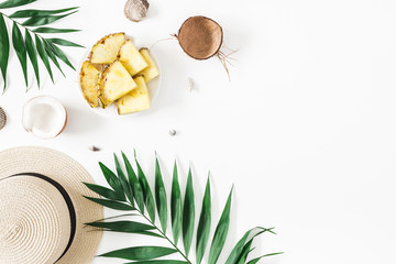 Summer composition. Tropical palm leaves, hat, pineapple, coconut on white background. Summer concept. Flat lay, top view, copy space