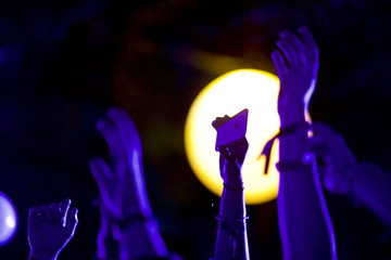 Revelers dance and take photos as Foster the People perform at the Firefly Music Festival in Dover, Delaware